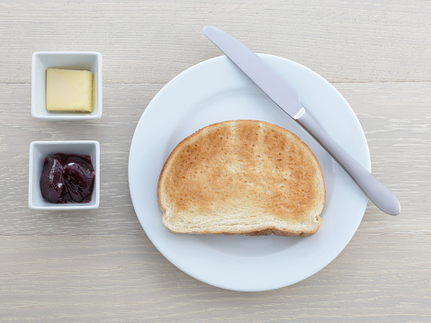 A Breakfast Plate Toast Knife Butter Jam Jelly On Wood Table